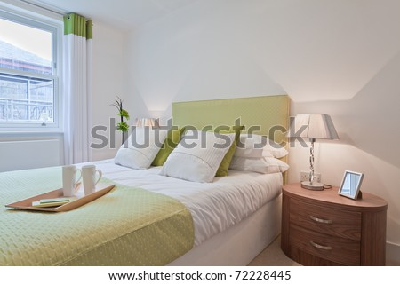 Modern bedroom dressed in a contemporary style with brightly colored fabrics - stock photo