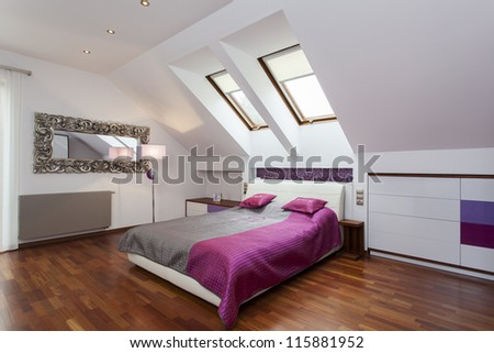 Modern bedroom in the attic of contemporary house - stock photo