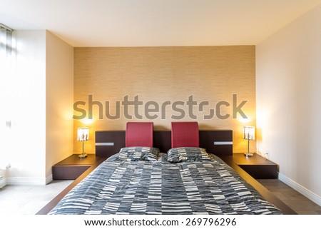 Modern bedroom interior with designer wood floor, bed in a luxury house. Interior design. - stock photo