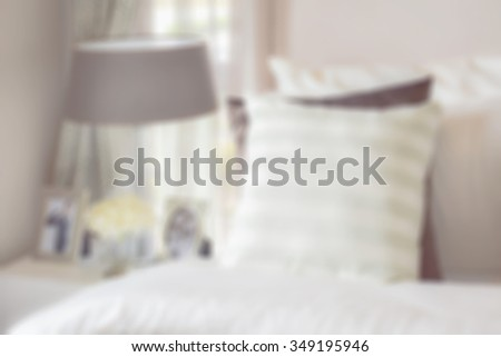 modern bedroom interior with green striped pillow on bed and bedside table lamp at home - stock photo