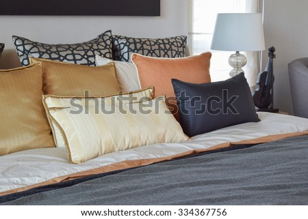 modern bedroom interior with orange and gold pillows on bed and bedside table lamp