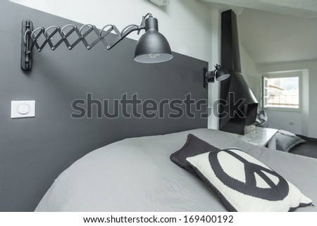 Modern bedroom with adjustable night lamp mounted on a wall. - stock photo