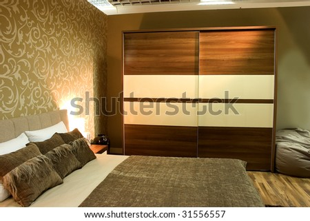 Modern bedroom with brown wardrobe and bed with two pillows. - stock photo