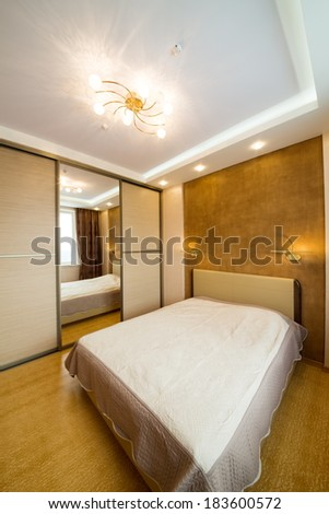 Modern bedroom with closet, large mirror and chandelier. - stock photo