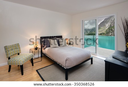 Modern Bedroom with rug and wooden deck and amazing lake mountain view.  - stock photo