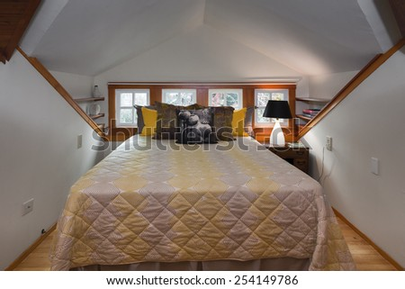 Modern bedroom with rug, window and wooden flooring with peaked roof. - stock photo