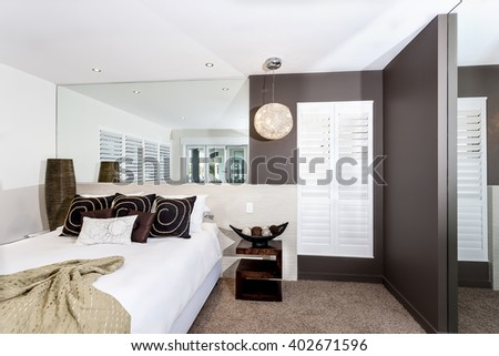 Modern bedroom with white sheets and pillows near a big mirror attached to the white wall - stock photo