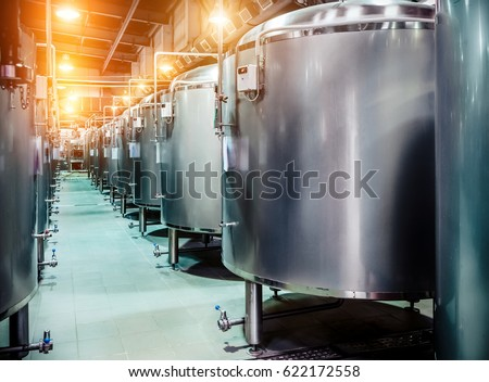 Modern Beer Factory. Rows Of Steel Tanks For Beer Fermentation And  Maturation. Spot Light