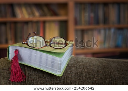 Modern Bible on Arm of a Chair with Reading Glasses with Lamp Reflection and Bookmark with Bookcase in Background with room or space for copy, text, your words.  Horizontal warm tones  - stock photo