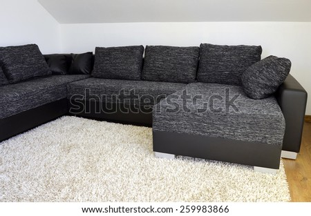 Modern black and white cloth sofa with black leather and pillows on shaggy carpet - stock photo