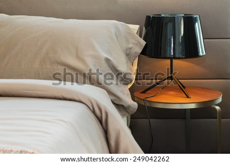 modern black lamp and brown pillow on bed - stock photo