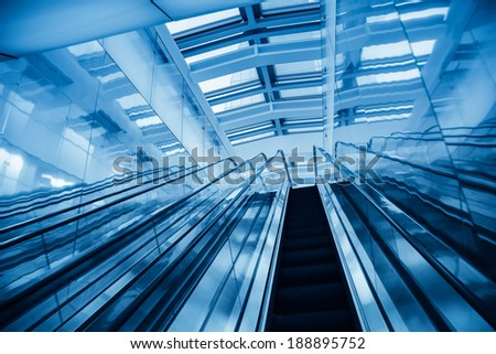 modern blue escalator in a glass building,abstract space
