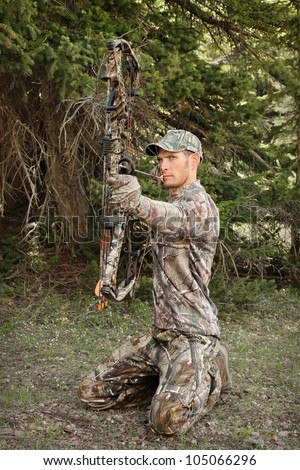 modern bow hunter kneeling in the woods drawing bow back - stock photo