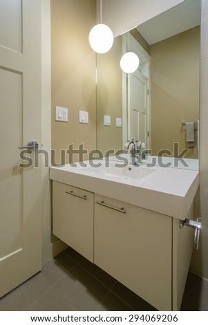 Modern bright bathroom with sink and large mirror. Interior design.