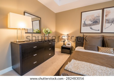 Modern bright bedroom interior with a large dresser and mirror. - stock photo