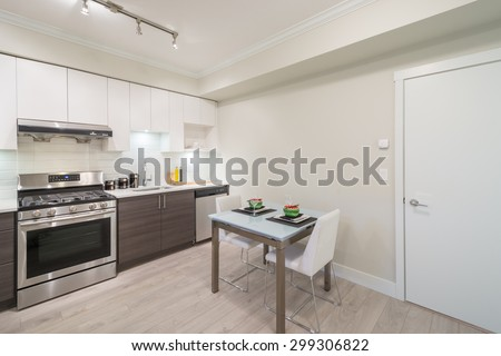 Modern, bright, clean kitchen interior with stainless steel appliances and dinner table in a luxury apartment. - stock photo