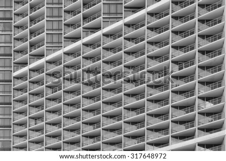 Modern building architecture side view in tones of black, white, and gray/grey, for use as an advertising backdrop/message. - stock photo