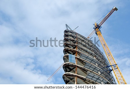 Modern building construction with yellow crane on a clear sky day. - stock photo