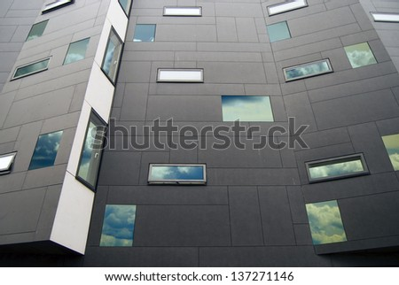 Modern building facade with sky reflecting in the windows - stock photo