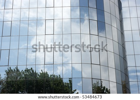 modern building glass reflects nature of trees and clouds