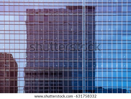 Modern building, Modern glass wall silhouettes of skyscrapers with another building reflection in the city, twilight tone