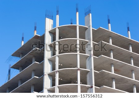 Modern building under construction against blue sky. - stock photo