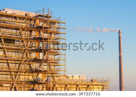Modern building under construction with blue sky - stock photo