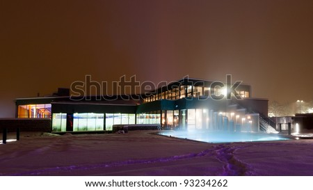 modern building with differnt light colors of a swimming pool at night on a winters day - stock photo