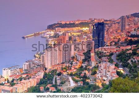 Modern buildings of Monte Carlo near the sea at dusk, Monaco, French Riviera - stock photo
