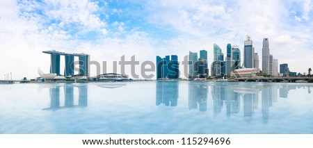 Modern buildings of Singapore skyline landscape in business district  with blue sky and reflection in water of Marina Bay - stock photo
