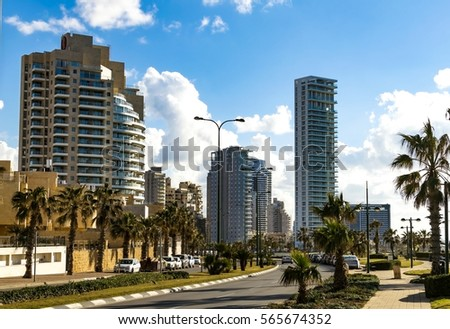 Modern buildings with palm trees on a background of blue sky
