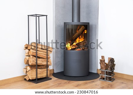 Modern burning stove next to a wood logs rack - stock photo