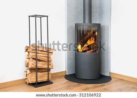 Modern burning stove next to a wood logs rack - stock photo
