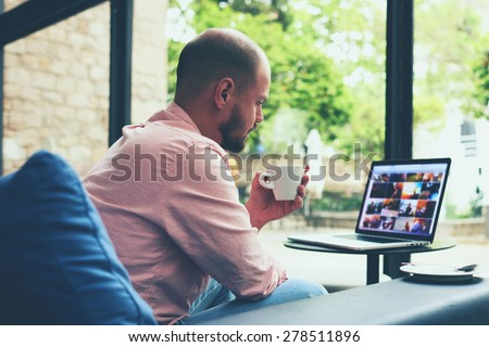 Modern business man connecting to wireless on his laptop computer during coffee break, male freelancer drink tea while working on notebook in loft studio, university student working at cafe or library - stock photo