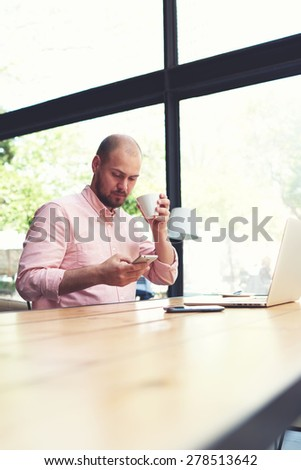 Modern business man connecting to wireless on his smart phone during coffee break, male freelancer reading text message oh cell phone while working in loft studio, university student working at cafe - stock photo