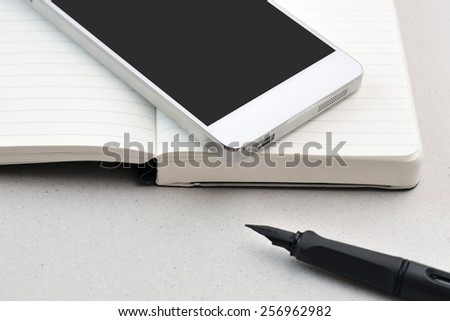 Modern business on the go-  smart phone, notebook, and pen, isolated
