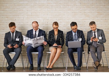 Modern business people in elegant suits sitting in row along wall - stock photo