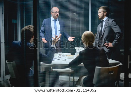 Modern business people sharing ideas and voicing opinions in office - stock photo