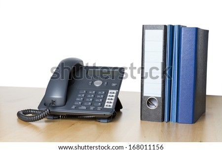modern business phone with ring binder an folder on wooden desk - stock photo