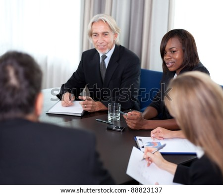 Modern business team writing notes and discussing on new business strategy together in a meeting at the office - stock photo