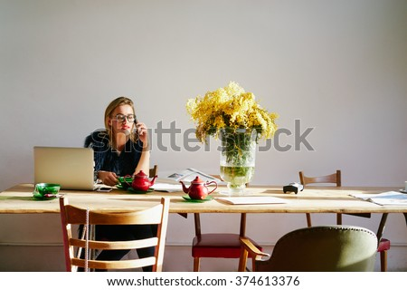 modern business woman discussing new project on the cell phone while sitting at a table in a coffee shop.attractive female freelancer working with a laptop computer in a cafe - stock photo
