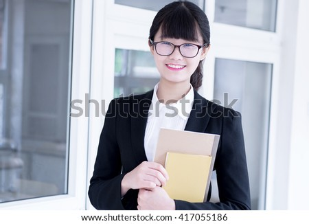 Modern business woman in the office, holding notebooks