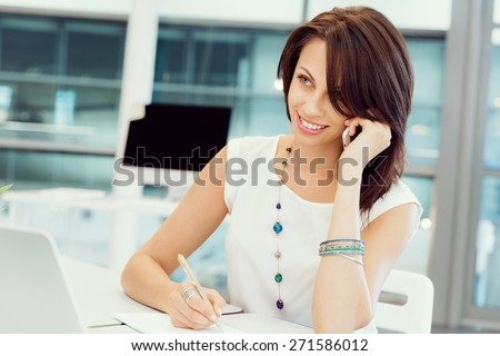 Modern business woman in the office with mobile phone - stock photo