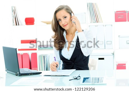 Modern business woman is talking on a cell phone at the office. - stock photo