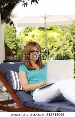 Modern business woman sitting at garden while working on laptop at home. - stock photo