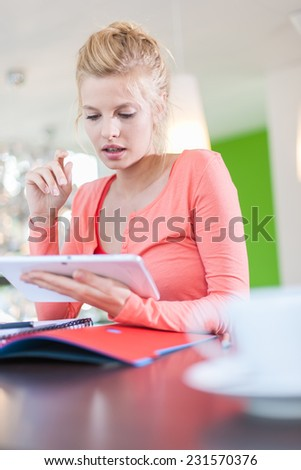 Modern business woman sitting at her contemporary office, using a digital tablet, cup of coffee at foreground - stock photo