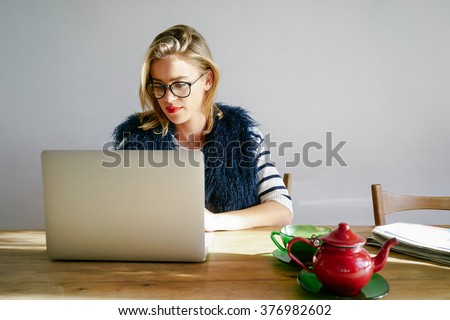 Modern business woman working on laptop computer during coffee break in coffee shop. Pretty blonde girl reading an e-book - stock photo