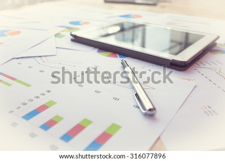 Modern business workplace with stock market data application , Pen and a digital tablet, on a wood table. - stock photo