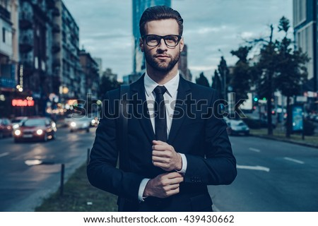Modern businessman. Confident young man in full suit adjusting his sleeve and looking away while standing outdoors with cityscape in the background - stock photo