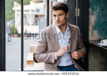 Modern businessman drinking coffee in cafe indoors